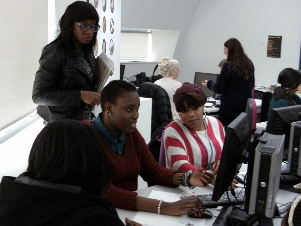 Yvonne Ellis with students working on leaflet design for Daughter Arise
