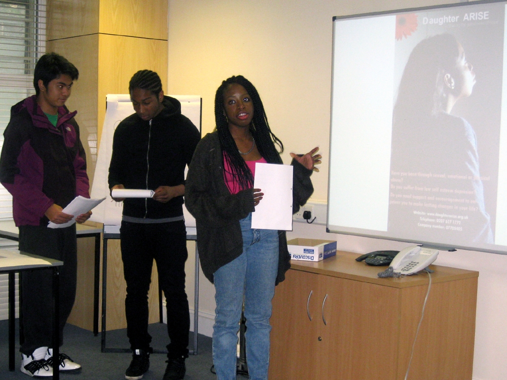 Students doing a presentation on leaflet design for Daughter Arise services